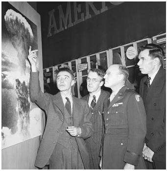 From left: J. Robert Oppenheimer, Professor. H. D. Smythe, General Nichols, and Glen Seaborg in 1946 looking at a photograph of the atomic blast at Hiroshima. The atomic bomb was developed in the Manhattan Project.