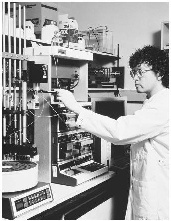 A scientist adjusts equipment used in fast protein liquid chromatography, which is used to isolate specific proteins from sample mixtures. Soluble proteins have a charge on their surfaces.