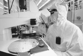A worker is testing silicon wafers at the Matsushita Semiconductor plant in Puyallup, Washington. Semiconductors are used in many different electronic products, such as computers, lasers, and solar panels.