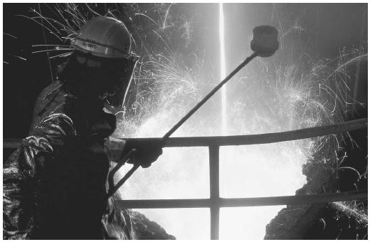 A steel worker is catching a sample of molten steel in a crucible during the manufacturing process.