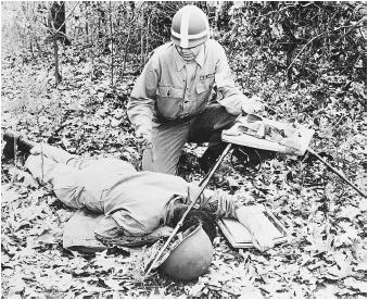 An army medic takes an x ray of a simulated injury during a field test of an atom-powered portable x-ray unit. Portable x-ray units are powered by thulium, obviating the need for electricity.